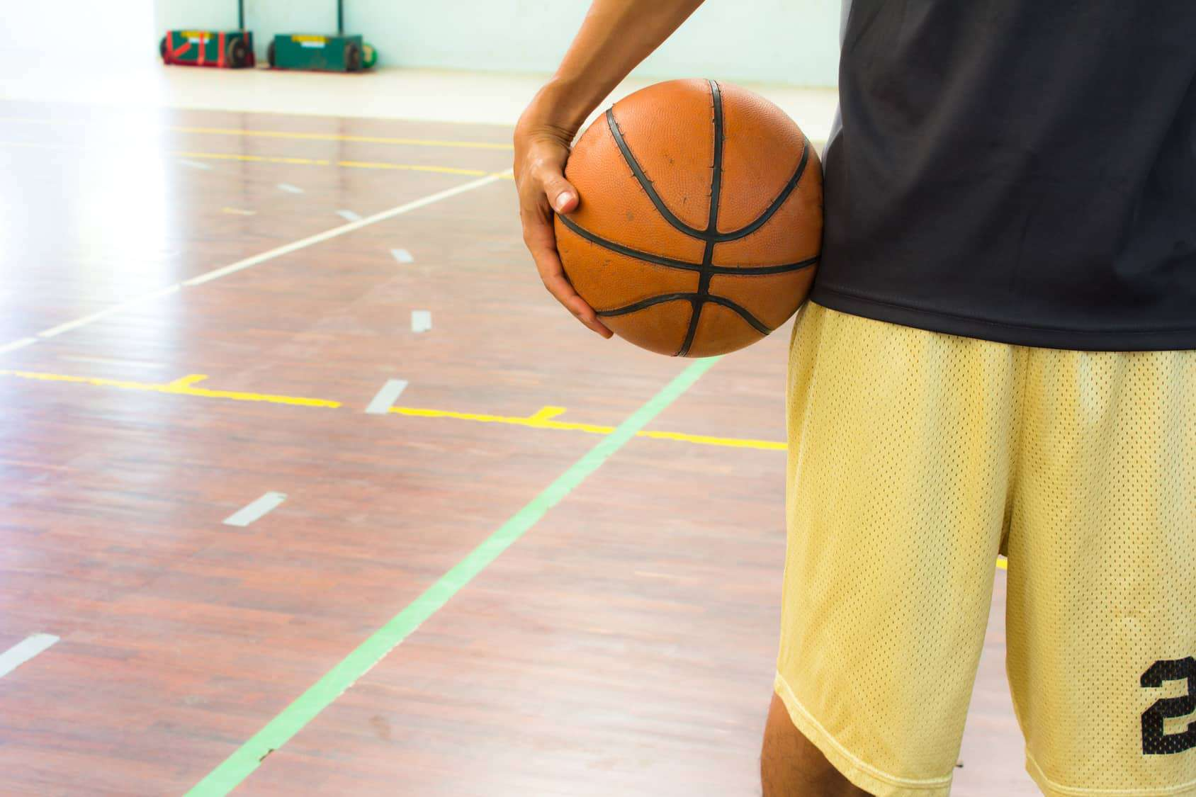 Player with basketball ball in gym